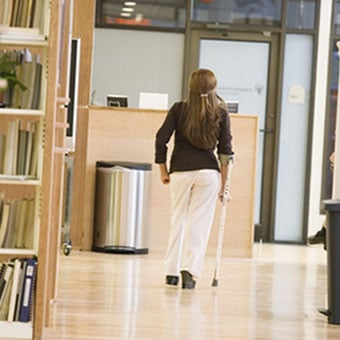 A woman with multiple sclerosis walks down a hallway.