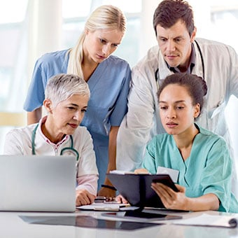 A group of doctors consulting on multiple sclerosis treatment for a patient.