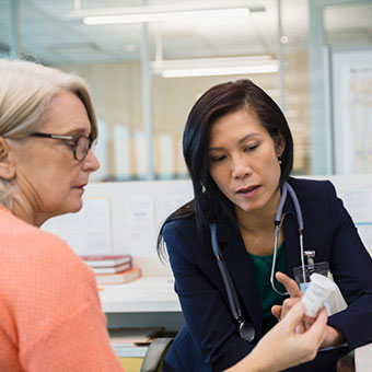 A doctor explains medication treatment to a patient with multiple sclerosis.