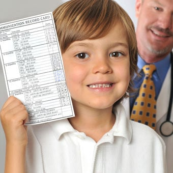 A young boy holds up his immunization record in the doctor's office.