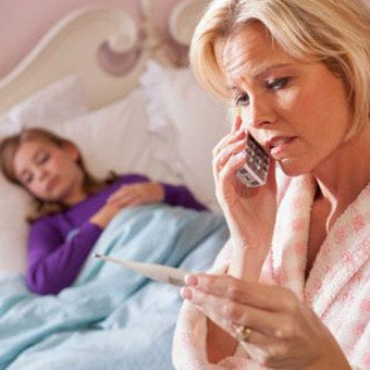 A mother reads a thermometer while her daughter is sick in bed.