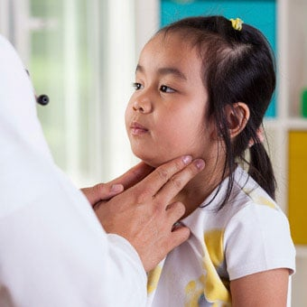 A doctor examines the lymph nodes of a little girl.