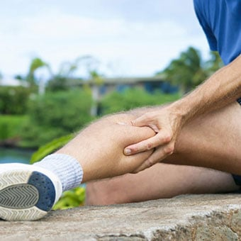 A runner experiences a muscle cramp in his calf.