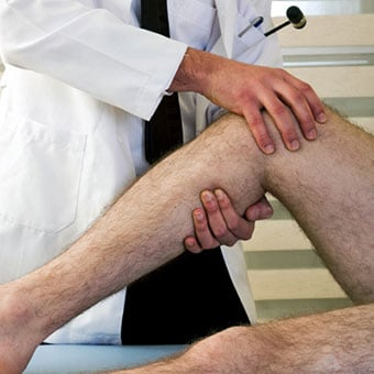 A doctor examines a patient's leg.