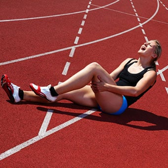 A female runner experiences a leg cramp on the track.