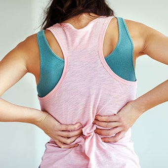 A woman experiences a muscle spasm in her back.