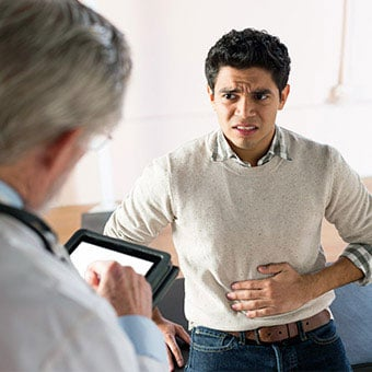 A patient discribing painful abdominal symptoms to his doctor.