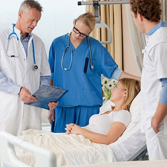 A group of doctors and nurses consulting with patient in a hospital room.
