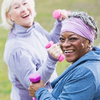 Two senior women exercising in the park.