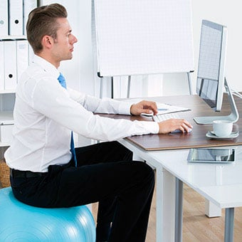 A businessman sits on a yoga ball at his desk to improve posture.