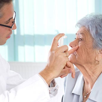 A doctor performs an eye exam on an elderly woman.