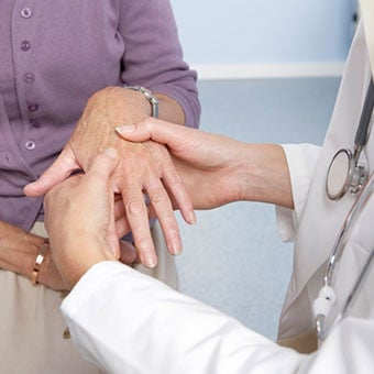A doctor examines a patient's hand for Raynaud's phenomenon.