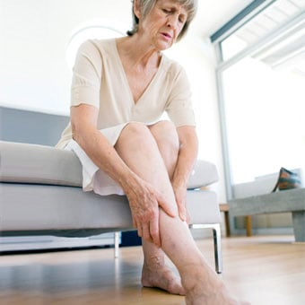 An older woman rubbing her aching legs due to restless leg syndrome.