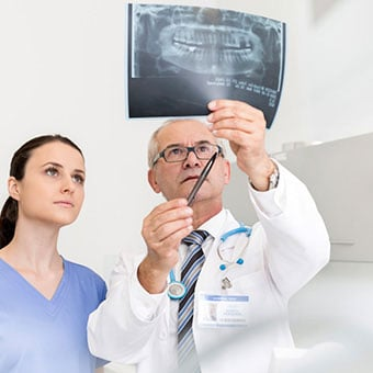 A dentist and his dental assistant review teeth in an X-ray to determine the need for root canal treatment.
