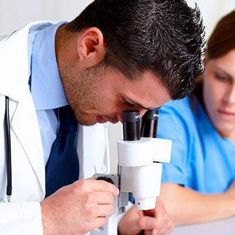 A doctor looks through a microscope for mites found from a skin scraping test for scabies.