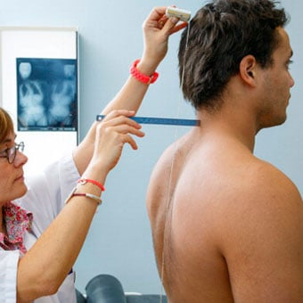A doctor performs a clinical exam and looks for signs of scoliosis in an adult male.