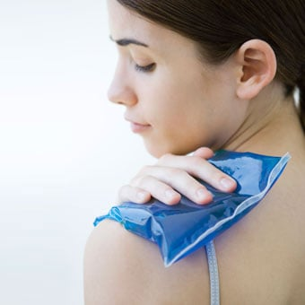 A woman places an ice compress on her shoulder.