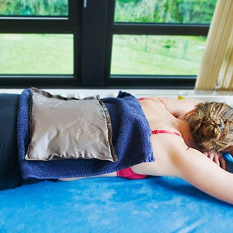 A woman uses an ice pack on her back to relieve her sacroiliac (SI) joint pain.