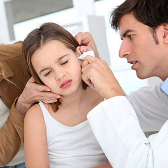 A doctor examines a young girl's ears for infection.