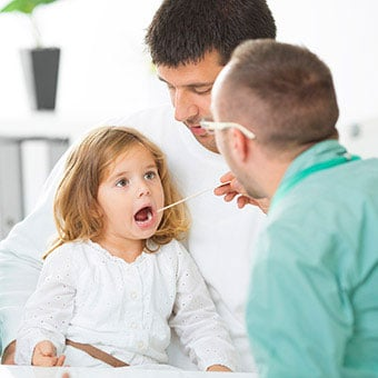 A doctor examines a young girl's mouth for strep throat.