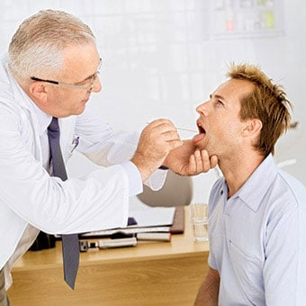 A doctor performs a throat culture on his patient to test for strep throat.