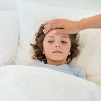 A boy sick in bed with an adult feeling his temperature by placing a hand on his forehead.