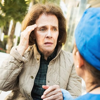 A doctor assists a confused senior woman.