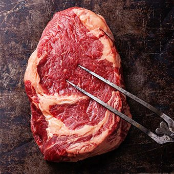 A raw cut of ribeye steak.