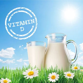 Vitamin D stamp on image with the sun, a jug, and glass of milk on the grass with daisies.