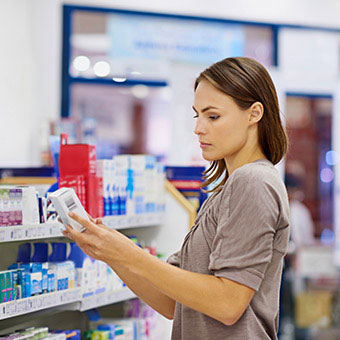 A woman reading the label of over-the-counter wart medication at the drug store.