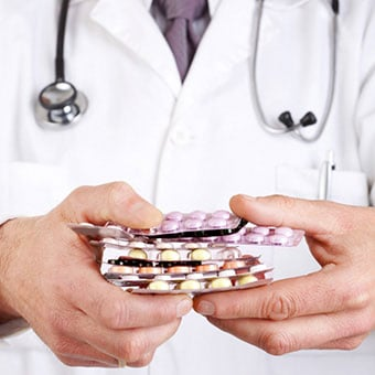 A doctor holds a variety of medications.