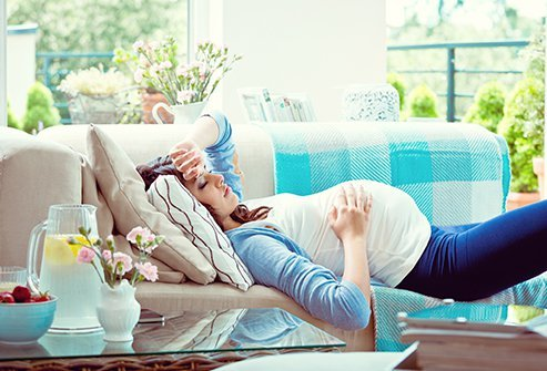 Pregnant woman laying down with her hand on her belly.
