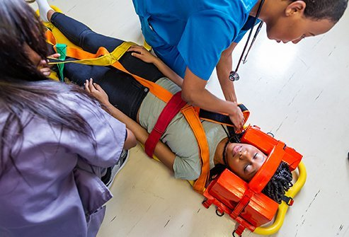 Paramedics stabilize a patient's spinal cord injury to prevent further damage.