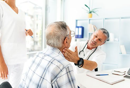 Picture of a doctor palpating an older man's throat.