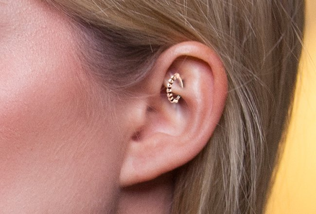 A rook piercing is done through the inner edge of the uppermost ridge in your ear.