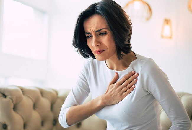 Chest pain on the left side above a female breast may be due to heartburn, a panic attack, gallbladder disease, gallstones, peptic ulcer and pneumonia.