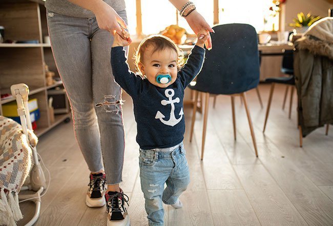 Babies typically take their first steps around 1 year of age.