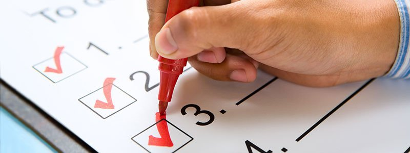 A male hand checking off a checklist with a red marker.