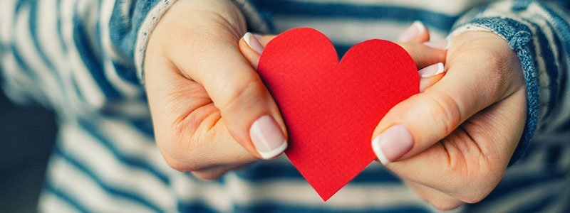 Cupped hands holding a heart-shaped object.