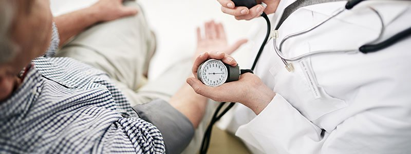 Doctor checking an overweight patient's blood pressure.