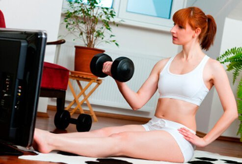 A woman exercises while watching a fitness DVD.