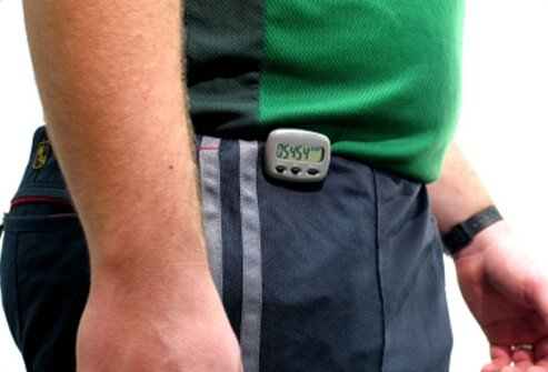 A man wears a pedometer while walking.