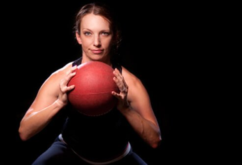 A woman works out with a medicine ball..