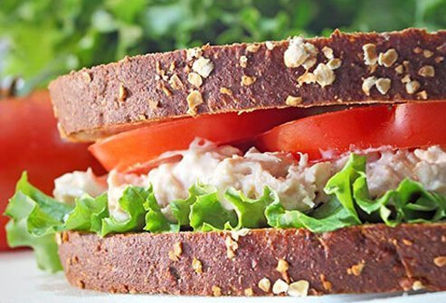 Photo of a tuna sandwich with lettuce and tomatoes.