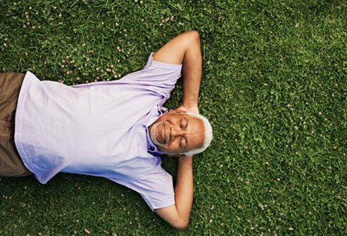 Photo of man laying on grass.