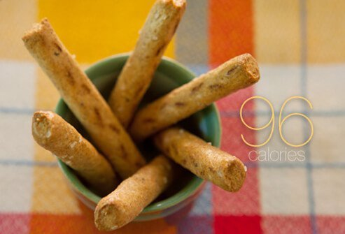 Six whole-grain pretzel sticks in a cup.