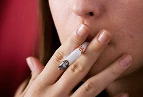 A woman smokes a cigarette.