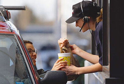 A woman picking up her food at a drive-thru window.