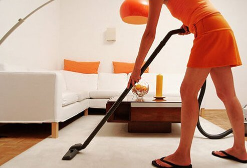 A woman cleaning her house to get the smell of smoke out.