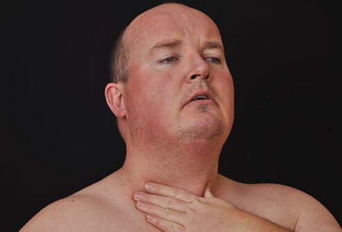 A man checks his neck and throat.